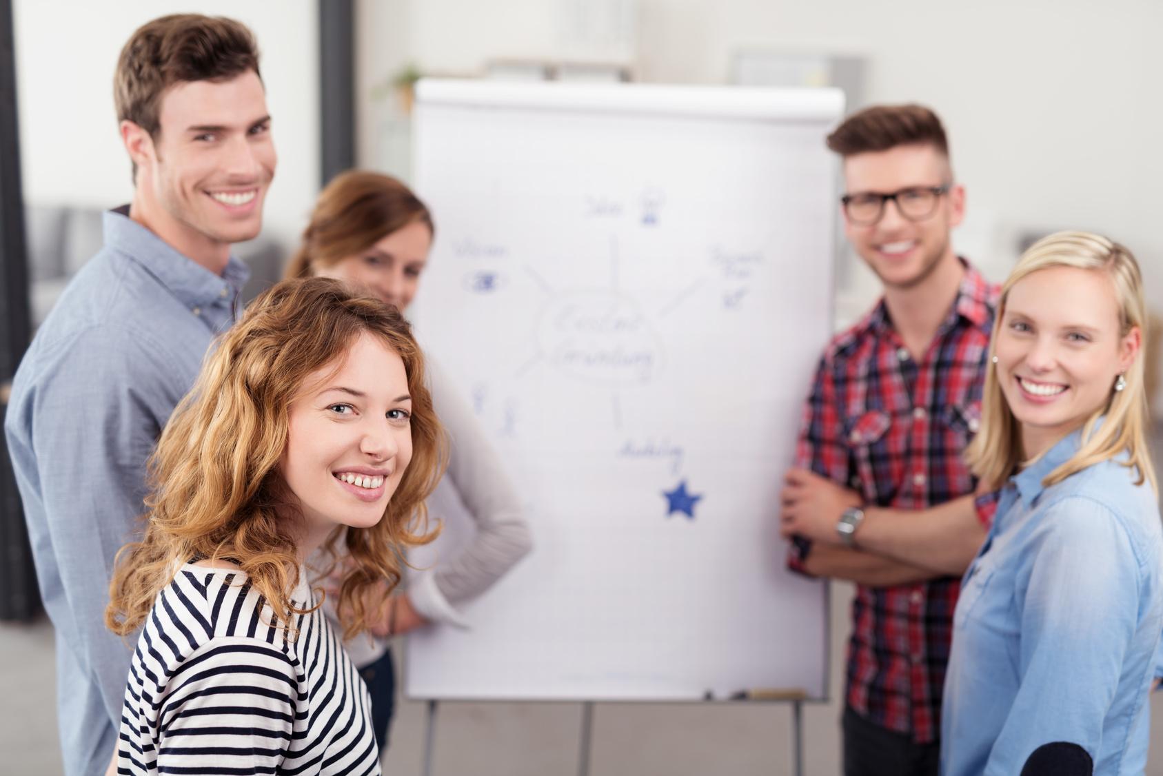 Gruppe Schüler steht vor einem Flipchart und erarbeitet Ideen